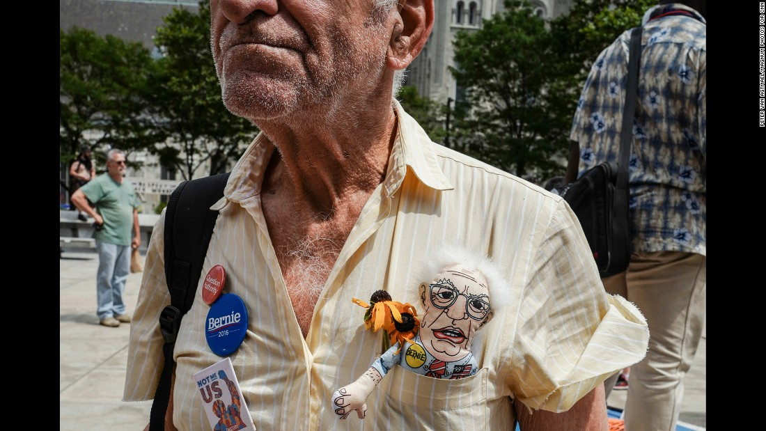 "A man attends a Sanders rally at City Hall. The senator has repeatedly asked his supporters to rally behind Clinton, even asking them in a text message to refrain from a floor protest as a ""personal courtesy."""