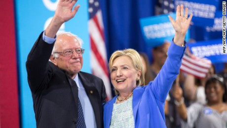 TOPSHOT - Presumptive Democratic presidential candidate Hillary Clinton and Bernie Sanders waves after speaking at a rally in Portsmouth, New Hampshire where she received Sanders' endorsement.  After months of bitter campaigning, Bernie Sanders on July 12 offered his long-awaited endorsement for Democratic presidential hopeful Hillary Clinton, saying he would work hard to help his former rival win the White House. The joint appearance at a high school in Portsmouth, New Hampshire was the culmination of weeks of talks between the two campaigns aimed at unifying the party in preparation for taking on Republican Donald Trump in November.  / AFP / Justin SAGLIO        (Photo credit should read JUSTIN SAGLIO/AFP/Getty Images)