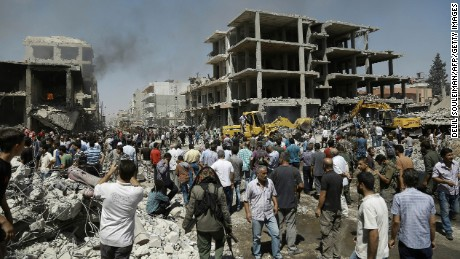 Syrians gather at the site of a bomb attack in Syria's northeastern city of Qamishli on Wednesday, July 27. A double bomb attack killed at least 14 people including civilians and left dozens wounded in a Kurdish-majority city in northeast Syria, the Syrian Observatory for Human Rights said.