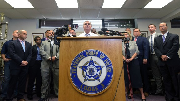 Gene Ryan, center, flanked by attorneys and accused police officers.