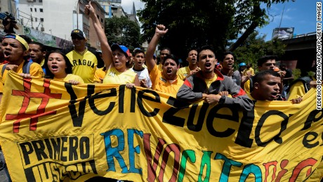 Members of the Venezuelan opposition shout slogans during a march to demand electoral power to activate the recall referendum against President Nicolas Maduro, in Caracas on July 27, 2016. Venezuela's opposition called protests Wednesday to demand electoral authorities allow a referendum on removing Maduro from power, a day after the government moved to outlaw the coalition. / AFP / FEDERICO PARRA        (Photo credit should read FEDERICO PARRA/AFP/Getty Images)