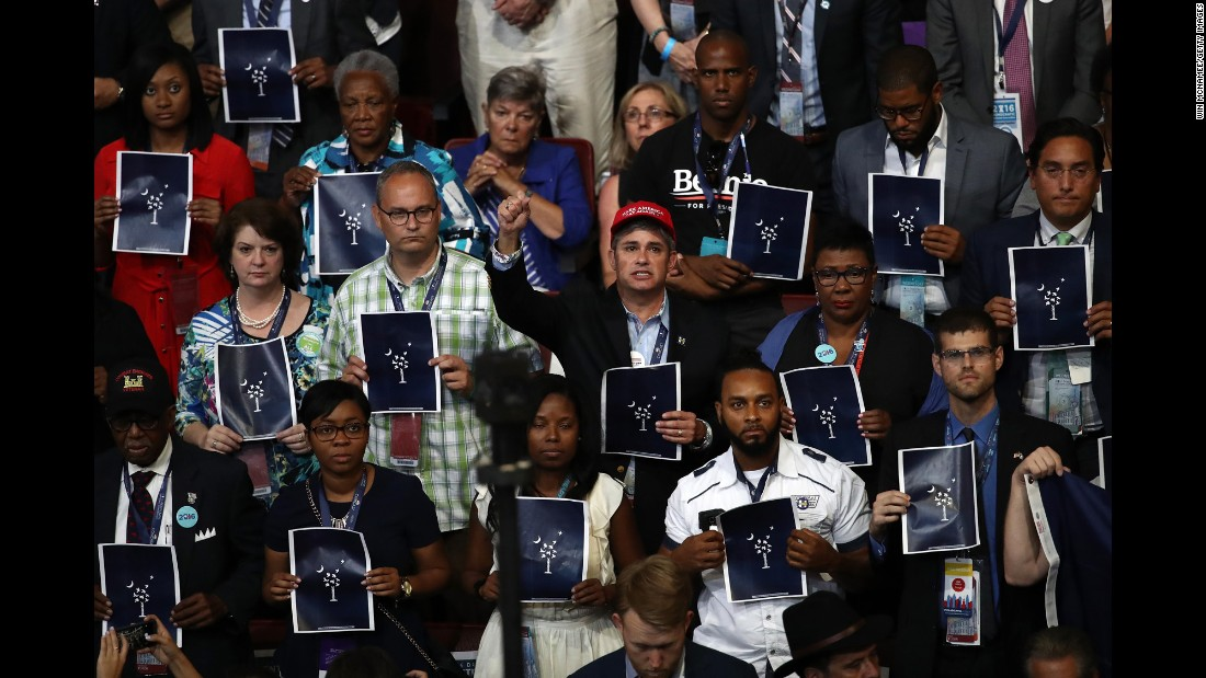 People hold up prints that pay respect to those who were killed in the Charleston, South Carolina, church shooting of June 2015. Two survivors of the shooting were speaking to the crowd.
