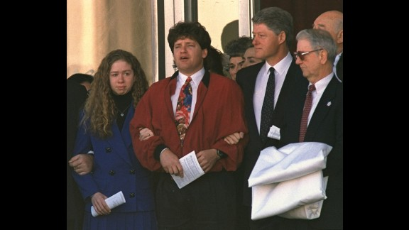 Chelsea holds the arm of her uncle Roger as the family leaves funeral services for the President