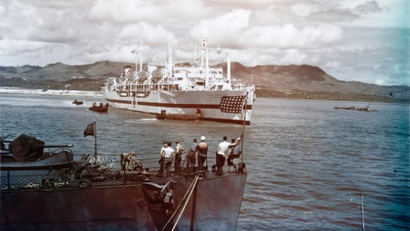 The USS Tranquillity arrives at Guam, carrying survivors of the USS Indianapolis sinking. Hundreds of men had been in the water for days, battling dehydration, exhaustion, exposure and sharks. A Navy plane spotted them by chance a few days after the sinking.