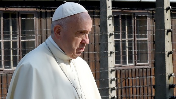 Pope Francis walks through the entrance of the former Nazi death camp of Auschwitz in Oswiecim, Poland on 29 July, 2016. Pope Francis is in Poland for an international Catholic youth festival with a mission to encourage openness to migrants.