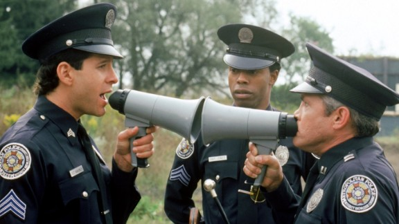 """Steve Guttenberg as Mahoney and G.W. Bailey as Captain Harris in conversation while Michael Winslow looks on in a scene from a """"Police Academy"""" film."""