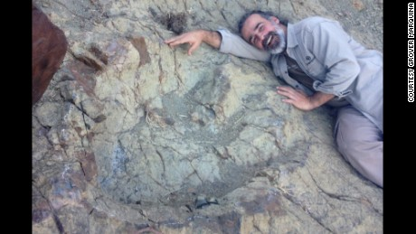 Paleontologist Sebastian Apesteguia lies next to a newly discovered dinosaur footprint in Bolivia.