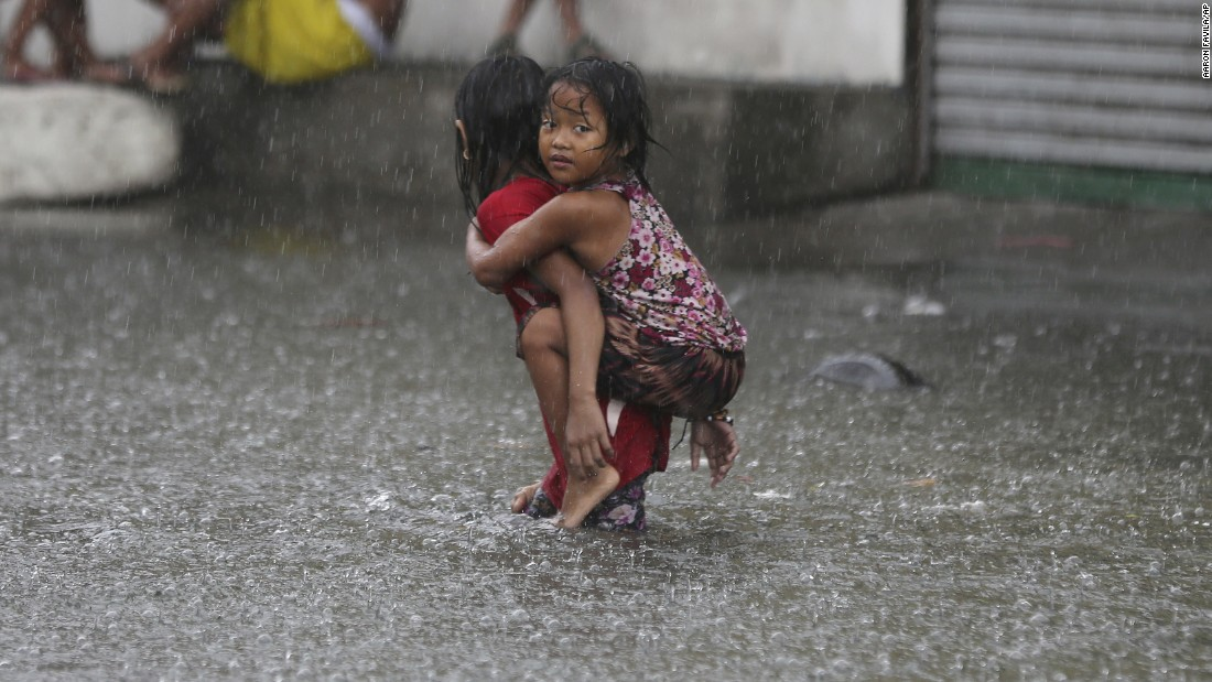A girl is carried along a flooded road in Mandaluyong, Philippines, as monsoon rains intensify on Friday, July 8.