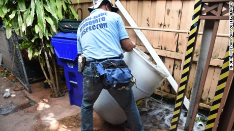 "Miami-Dade mosquito control worker Carlos Vargas dumps a barrel of standing water that can incubate the Aedes aegypti mosquito larvae at a home in Miami, Florida, on June 08, 2016.  Of the forty different types of mosquito found in Miami -Dade the Aedes aegypti mosquito or yellow fever mosquito is responsible for transmitting diseases such as the Zika Virus.  / AFP / RHONA WISE / TO GO WITH AFP STORY by Leila MACOR, ""Florida health warriors deploy in war on Zika""        (Photo credit should read RHONA WISE/AFP/Getty Images)"