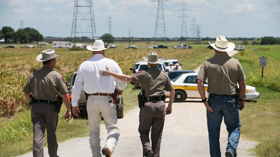 Texas DPS Trooper Robbie Barrera, center right, puts her arm around Caldwell County Sheriff Daniel Law as he arrives on the scene of a hot air balloon crash Saturday.