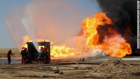 Oil workers and firemen try to extinguish flames at the Khabbaz oil field  near Kirkuk on June 1 after an attack.