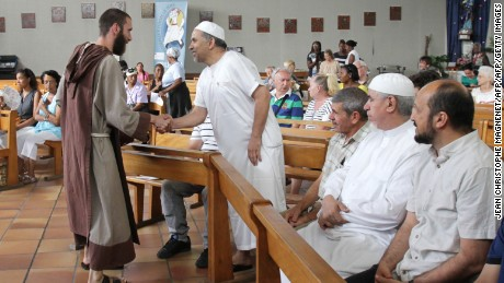 A Catholic monk welcomes Muslims to a mass in Nice, France, where people gathered to mourn a priest slain by jihadists.