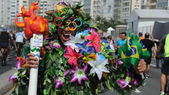 """A man disguised as Batman holds a fake Olympic torch reading """"Shame"""" during a protest against suspended president Dilma Rousseff and former president Luiz Inacio Lula Da Silva, at Copacabana beach in Rio de Janeiro, Brazil, on July 31, 2016. Protesters took to the streets of Brazil on Sunday to demand the final leaving of suspended President Dilma Rousseff or to defend her continuance, just five days before the start of the Rio 2016 Olympic Games. / AFP / TASSO MARCELO        (Photo credit should read TASSO MARCELO/AFP/Getty Images)"""