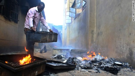 A student at a boys school in Kisii, Kenya, salvages personal effects from a smoldering dormitory building.