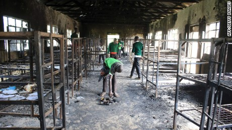 Students of St. Peter's-Nyamesocho in Kisii  rummage through a burned dormitory for salvageable items.