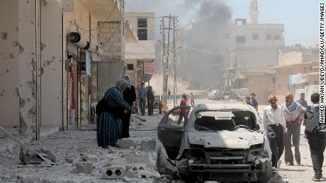 A woman inspects a damaged car after the Russian army planes carried out an airstrike over residential areas in Etarib district of Aleppo, Syria on August 02.