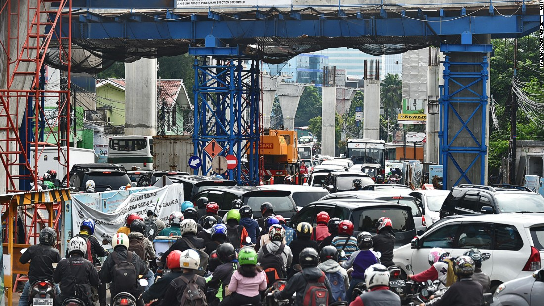 Motorists suffer through a traffic jam in Jakarta on February 4, 2016 near a construction site. Indonesia lacks a mass-transport system, forcing its increasingly affluent 260 million people to rely heavily on private transport.