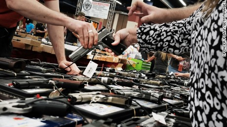 A woman tries a pistol at a gun show where thousands of different weapons are displayed for sale on July 10, 2016, in Fort Worth, Texas.