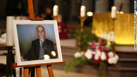 A picture of the slain priest appears at his funeral. His killing in a house of worship has rocked France.