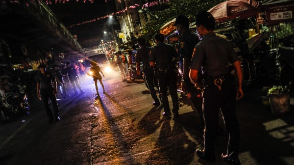 Police patrol a shanty community at night during curfew on June 8, 2016 in Manila.