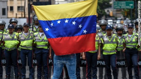 A member of the Venezuela's opposition shows a national flag in front of National policemen during a demonstration in Caracas on July 27, 2016. Venezuela's opposition called protests Wednesday to demand electoral authorities allow a referendum on removing President Nicolas Maduro from power, a day after the government moved to outlaw the coalition. The opposition is hoping pressure from Venezuelans fed up with the country's deep recession, food and medicine shortages, and mounting chaos will force the authorities to allow a recall referendum against Maduro. / AFP / JUAN BARRETO        (Photo credit should read JUAN BARRETO/AFP/Getty Images)