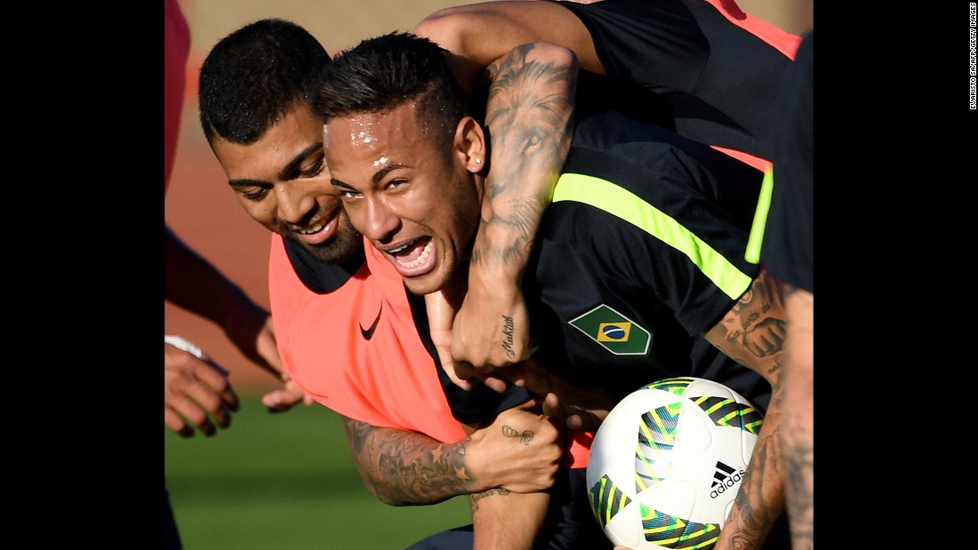 Brazilian soccer players Neymar, right, and Gabriel Jesus joke during a training session in Brasilia, Brazil, on August 1.