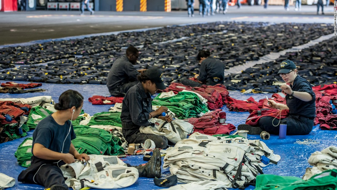 On August 3, 2016, Reagan crew prepare for an inspection of life preservers in the hangar bay of the USS Ronald Reagan. In the foreground, sailors work on life preservers for the flight deck crew. There are about 700 of those aboard. In the rear are general life jackets, there are about 7,000 of those.