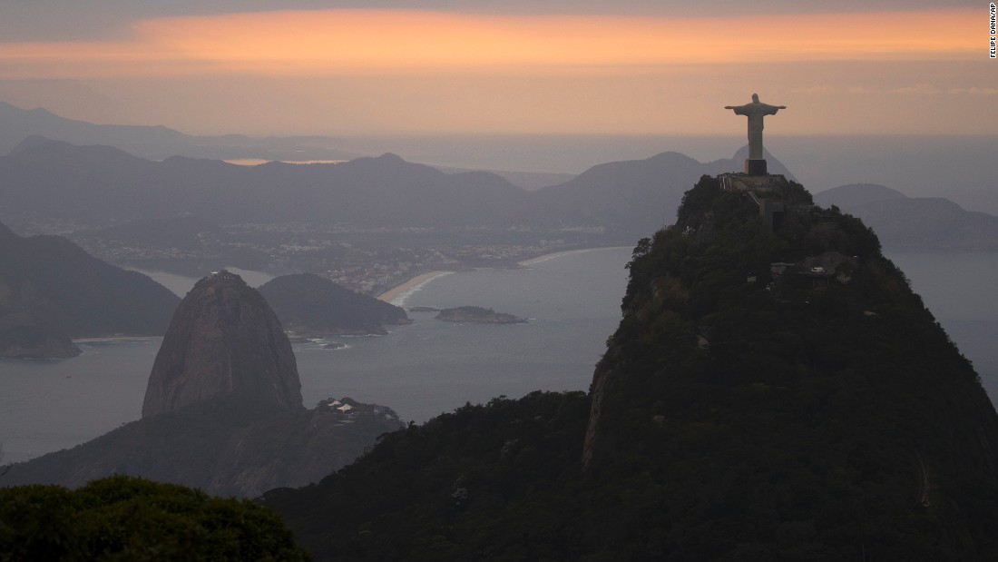 The sun rises over the Christ the Redeemer statue and Sugarloaf Mountain on August 4.