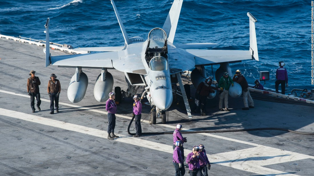 Sailors on the flight deck catch their breath alongside an F/A-18E Super Hornet during a break in flight operations aboard the USS Ronald Reagan.