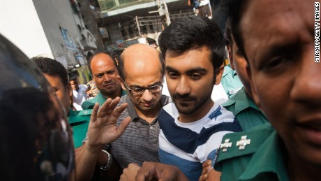 Bangladesh police escort Hasnat Karim (center-left) and Tahmid Hasib (center-right) toward court on August 4, 2016.