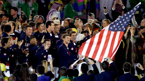 U.S. swimmer Michael Phelps, the most decorated Olympian of all time, carries the American flag into the Maracana Stadium.