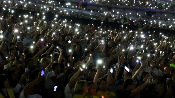 Spectators hold up their phones during the event.