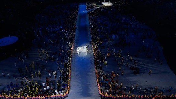 The Olympic flag is carried into the stadium.
