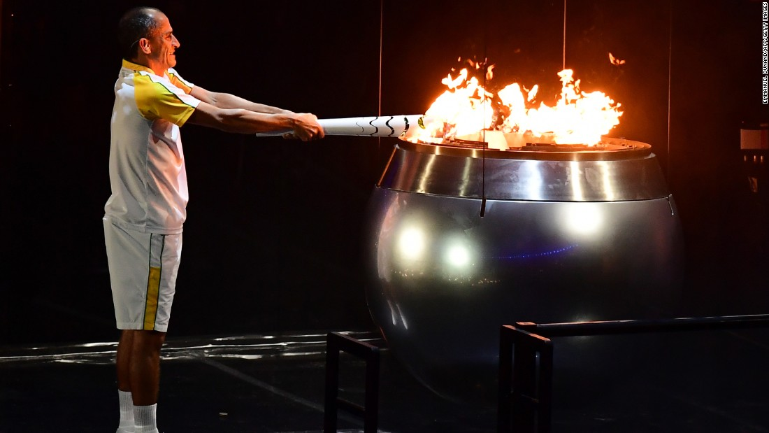 Vanderlei Cordeiro de Lima, a former Brazilian long-distance runner, lights the Olympic cauldron. De Lima was leading the Olympic marathon in 2004 when he was attacked by a protester near the end of the race. He ended up finishing third, but the graceful way he handled the disappointment won him plaudits around the world for his sportsmanship.