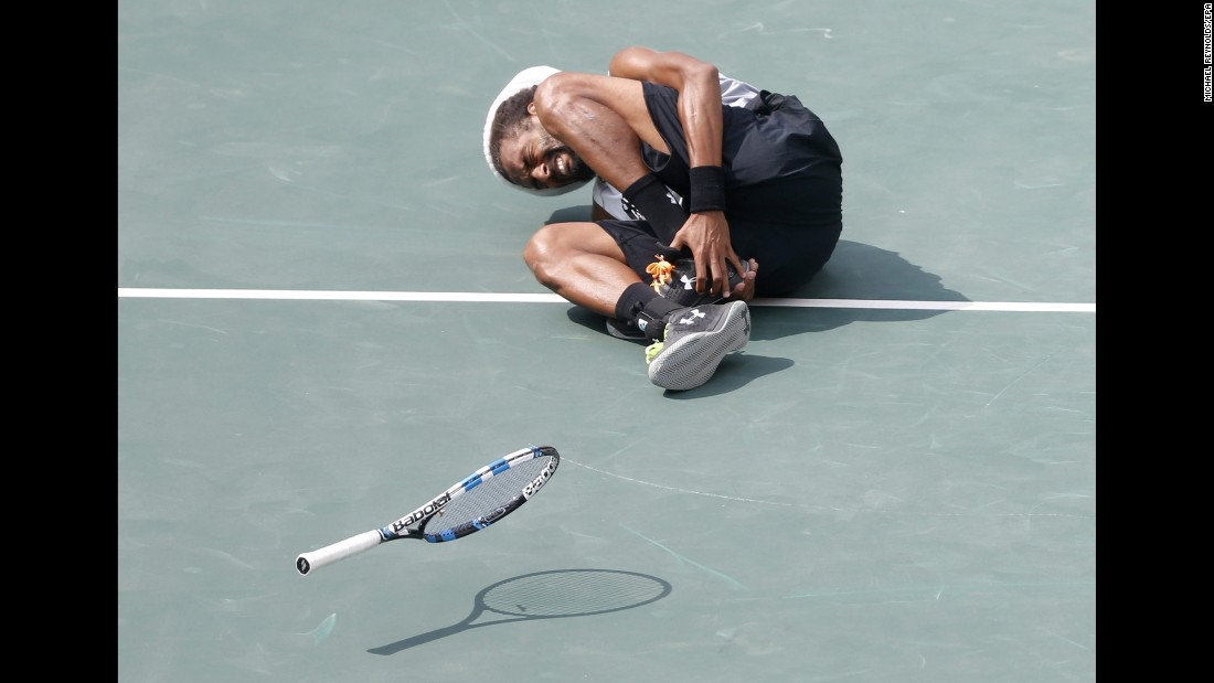 Dustin Brown of Germany grimaces after hurting his ankle during his match against Thomaz Bellucci of Brazil. Brown would later exit the game.