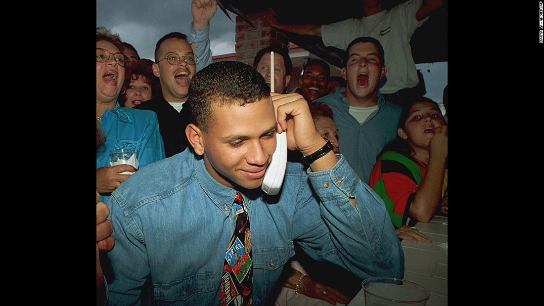 Alex Rodriguez listens on the telephone as the Seattle Mariners ask him to join their team amid cheers from his mother, Lourdes, back left, and friends in Miami, Florida, on June 3, 1993.  Rodriguez, then 18, was the top draft choice in baseball's amateur draft.