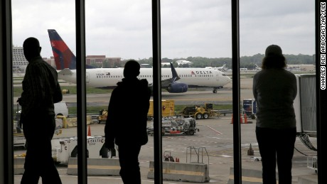 FILE - In this April 14, 2015, file photo, Delta Air Lines passengers watch as a Delta plane taxis at Atlanta's Hartsfield International Airport in Atlanta. Delta Air Lines grounded flights scheduled to leave Monday, Aug. 8, 2016, after experiencing unspecified systems issues. Confirmation of the troubles came in an official account that responds to customers via Twitter. The airline declined to immediately comment by phone and it was unclear whether all its flights were affected. (AP Photo/Charles Rex Arbogast, File)