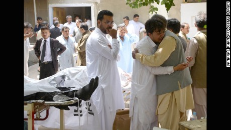 People react beside the bodies of victims following a bomb explosion at a government hospital in Quetta, Pakistan, on Monday, August 8.