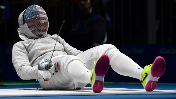 Ibtihaj Muhammad, the first American to wear a hijab in the Olympics, reacts on the piste as she competes against France's Cecilia Berder in a fencing bout. Berder won 15-12 to advance to the quarterfinals of the sabre competition.