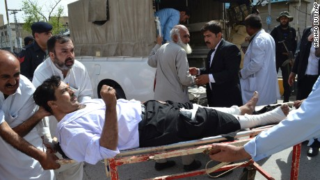 People carry an injured lawyer to a hospital following a bomb blast in Quetta, Pakistan, Monday, Aug. 8, 2016. A powerful bomb went off on the grounds of a government-run hospital Monday, killing dozens of people, police said. (AP Photo/Arshad Butt)
