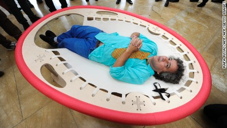 "Brazilian artist Ernesto Neto lies on his artwork ""Looking at the Sky"" as he looks at his installation ""The Falling Body"" (out of frame) during the presentation of his exhibition ""The Body That Carries Me"" on February 13, 2014 at the Guggenheim Bilbao museum in the northern Spanish Basque city of Bilbao.  AFP PHOTO / RAFA RIVAS        (Photo credit should read RAFA RIVAS/AFP/Getty Images)"