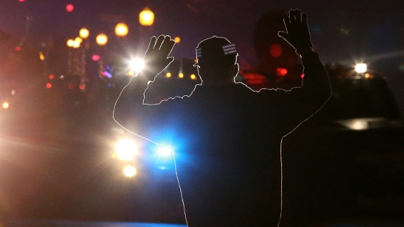 """When 18-year-old Michael Brown was fatally shot by Darren Wilson in August 2014, it set off a chain reaction that led to protests nationwide. These images are some of the most iconic from that period, such as this photo of a protester who adopted the """"hands up"""" stance seen in many demonstrations. It was used because some witnesses said that Brown had his hands up when he was killed. Click through the gallery for more images surrounding the protests."""
