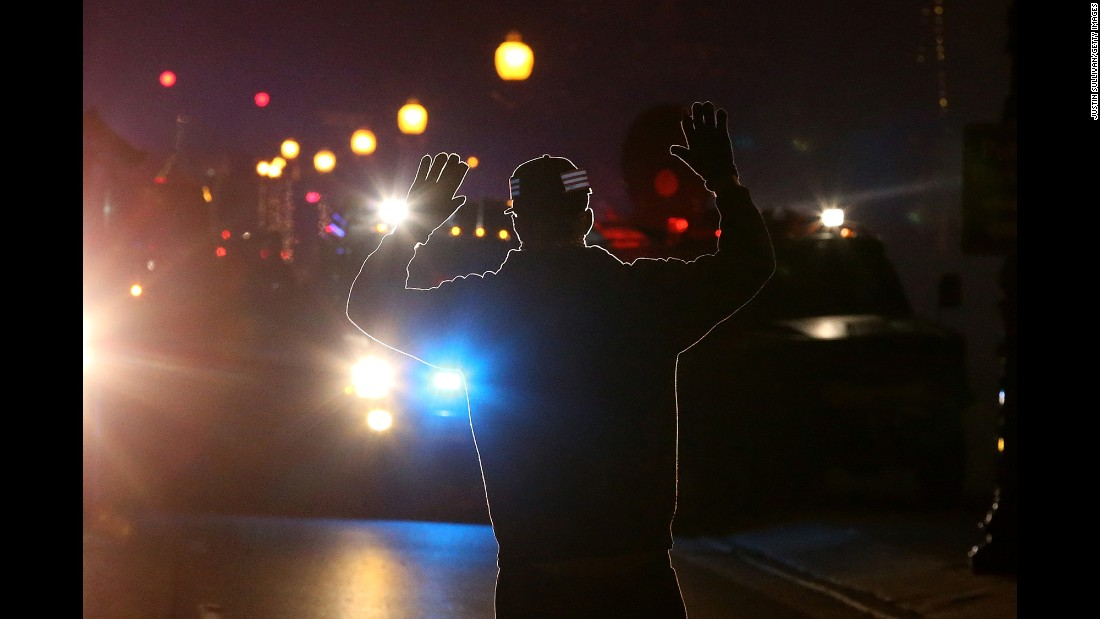 "When 18-year-old Michael Brown was fatally shot by Darren Wilson in August 2014, it set off a chain reaction that led to protests nationwide. These images are some of the most iconic from that period, such as this photo of a protester who adopted the ""hands up"" stance seen in many demonstrations. It was used because some witnesses said that Brown had his hands up when he was killed. Click through the gallery for more images surrounding the protests."