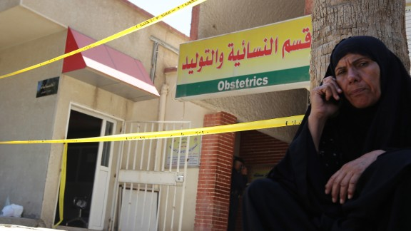 A woman speaks on the phone Wednesday outside Yarmouk hospital in west Baghdad, Iraq.
