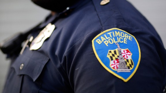 FILE- In this March 31, 2016, file photo, Baltimore Police Department Officer Jordan Distance stands on a street corner during a foot patrol in Baltimore. Baltimore police officers routinely discriminate against blacks, repeatedly use excessive force and are not adequately held accountable for misconduct, according to a harshly critical Justice Department report being presented Wednesday, Aug. 10, 2016. (AP Photo/Patrick Semansky, File)