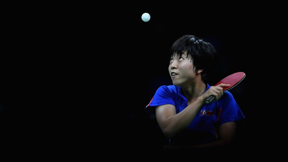 North Korean table tennis player Kim Song-i focuses on the ball during her semifinal match against Ding Ning of China. Ding advanced to the gold-medal match, which she won.