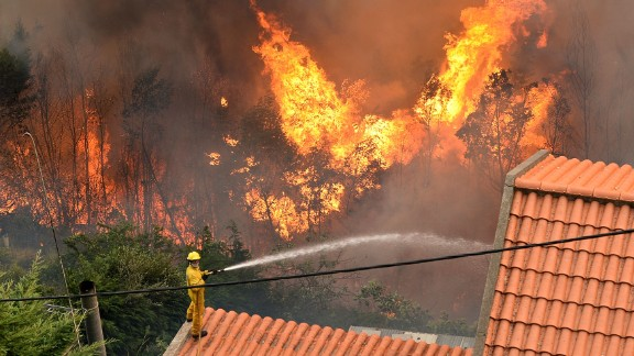 A firefighter works to extinguish a fire at a home in Funchal.