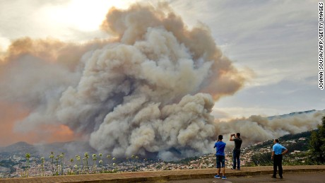 Bystanders photograph the smoke cloud rising from a wildfire on Madeira.