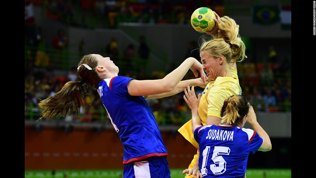 Russian handball player Victoria Zhilinskayte, left, competes against Sweden's Linnea Torstensson during a preliminary match.