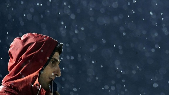 A fan watches archery under pouring rain in Rio de Janeiro.